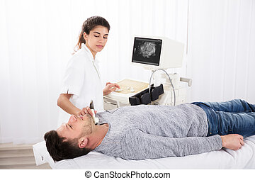 Man Getting Ultrasound Of A Thyroid From Doctor