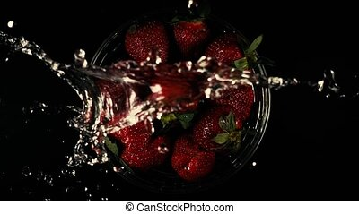 The water falls on the strawberry. Slow motion