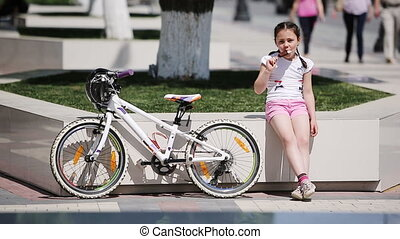 Cute little girl eating ice cream in the city park in...