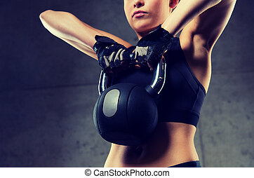 close up of woman with kettlebell in gym - fitness, sport,...