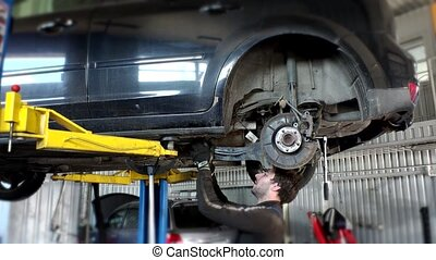 auto mechanic man replacing silent block with new one. -...