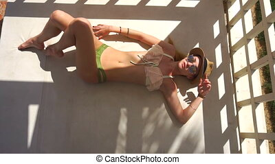 sexy young girl in a bathing suit hat and glasses sunning at...