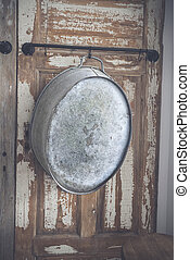 Old stylish iron tub hanging on a wooden wall
