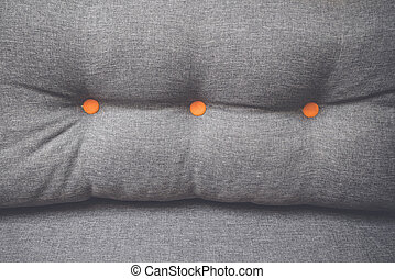 Pillow in grey color with orange buttons