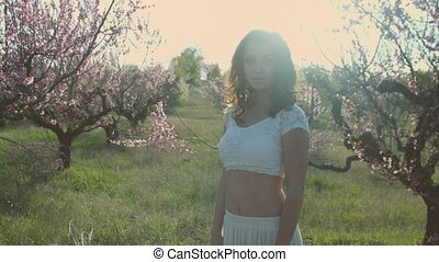 Cute girl walking in the flowering peach garden - Cute girl...