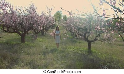Lovely girl standing in the blossoming garden and begins to...
