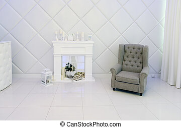 White room with decorative fireplace, candles, armchair, soft walls