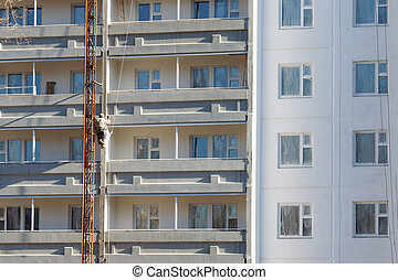 Climber worker hanging on ropes to painting of high rise building at sunny day