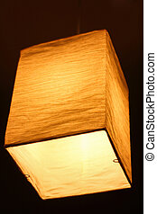 Textile lamp shape of a parallelepiped shines a warm yellow...