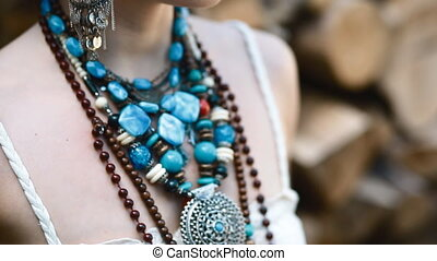 Details of ethnic jewelery. Camera moves from up to bottom.