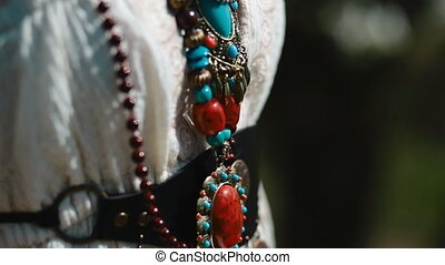 Details of ethnic jewelery. Camera moves from the bottom to...