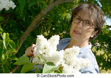 senior woman in her garden with flowers