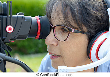 woman with headphones, using camera dslr - A mature woman...