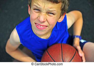 Smiling boy with a basketball sitting on court