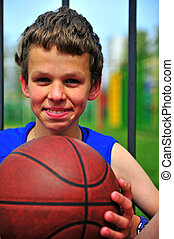 Portrait of basketball player with a ball outdoors