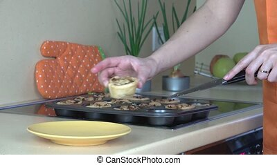 woman hands take out baked meat cup cakes from cookie sheet and put in dish