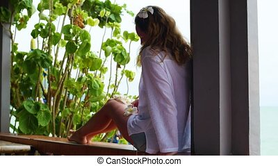 The girl sits on the terrace and looks towards the...