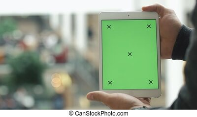 Male hands using tablet with green screen in shopping mall