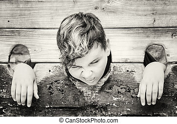 Young caucasian boy in medieval pillory, colorless