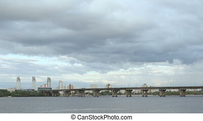 The sky is covered with clouds over a wide river - Tight sky...
