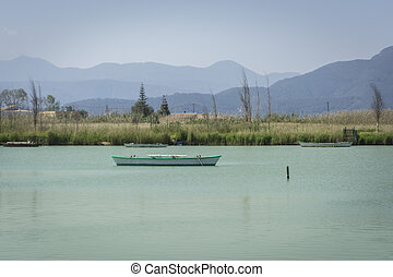 Calm lake with fishing boats. Fresh water lagoon in Estany de cullera. Valencia, Spain