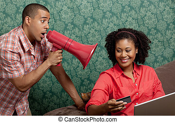 Man using megaphone as woman shops online at home