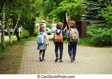 Little school students hurry on occupations. Behind...