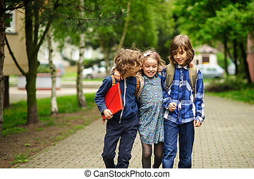 Three little friends go to school. Behind shoulders at...