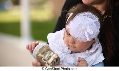 Close-up of the cute little baby-girl sitting on the arms of...