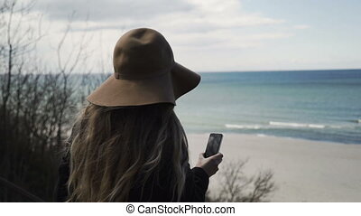 The Lonely Woman With The Smartphone in a Hand Looks at the...