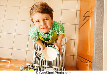 Cute boy holding bowls standing next to dishwasher -...