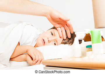 Boy crying while father measuring his temperature