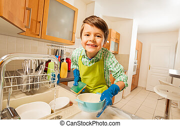 Cute kid boy doing the dishes in rubber gloves - Portrait of...