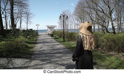 A young woman in a coat and hat, park goes to the sea.