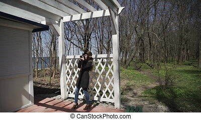 Young woman in a white wooden pergola in a gray coat and fashion hat shooting photos with DSLR camera