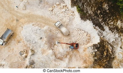 Excavator loads truck in quarry. Philippines,Siargao. -...
