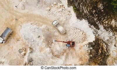 Excavator loads truck in quarry. Philippines,Siargao. -...