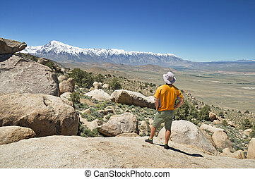 Man Looking At Mountains - the back of a man looking at the...
