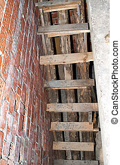 Wooden staircase in brick building under construction.
