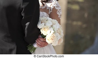 Elegant bride and groom posing together outdoors on a wedding day. Bride holding a white rose bouquet while standing next to groom. bride in a dress standing and holding a wedding bouquet