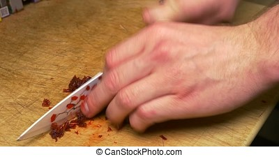 Man's hand with knife cutting pipe tobacco for Hookah. Tobacco preparation. Dry fruits for hookah. Hookah tobacco. Hookah tobacco in bowl. Preparation of a mixture for Smoking.