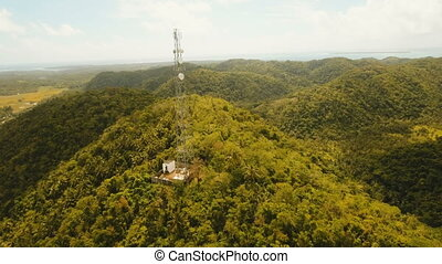 Telephone signal tower among green forest and mountains....