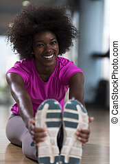woman in a gym stretching and warming up before workout