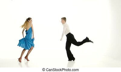 Pair of graceful dancers perform tango on white studio...