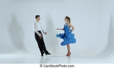 Couple of graceful dancers perform rumba on white...