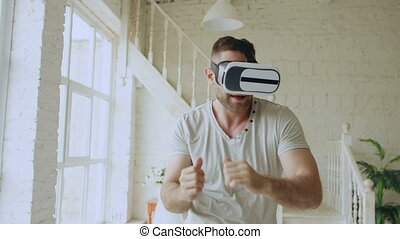 Cheerful young man dancing while getting experience using 360 VR headset glasses of virtual reality in bedroom at home