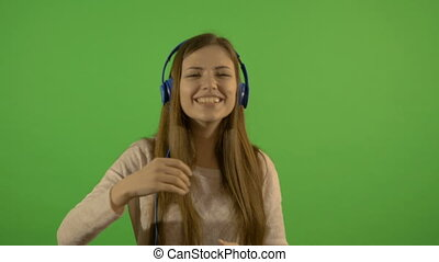A beautiful young white model listens to music through...