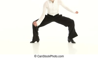 Close-ups of legs of dancing rumba man in white studio