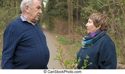 An elderly couple is talking on a walk in the park. Swear,...