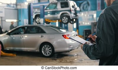 Mechanic checks part of cars in a garage workshop - auto...